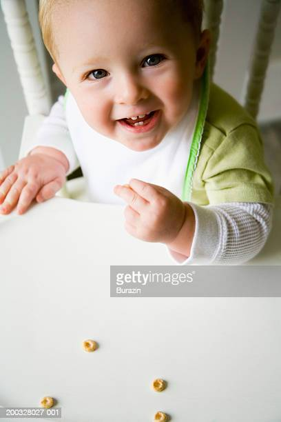 Baby boy (12-15 months) in high chair eating cereal, portrait