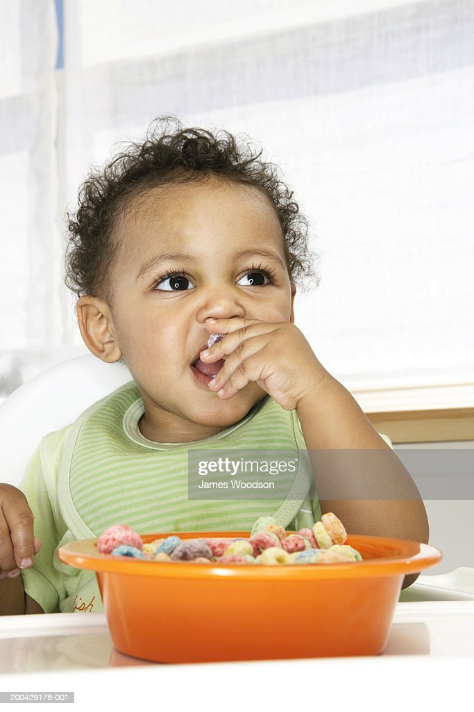 Baby boy (18-24 months) in high chair eating cereal with fingers