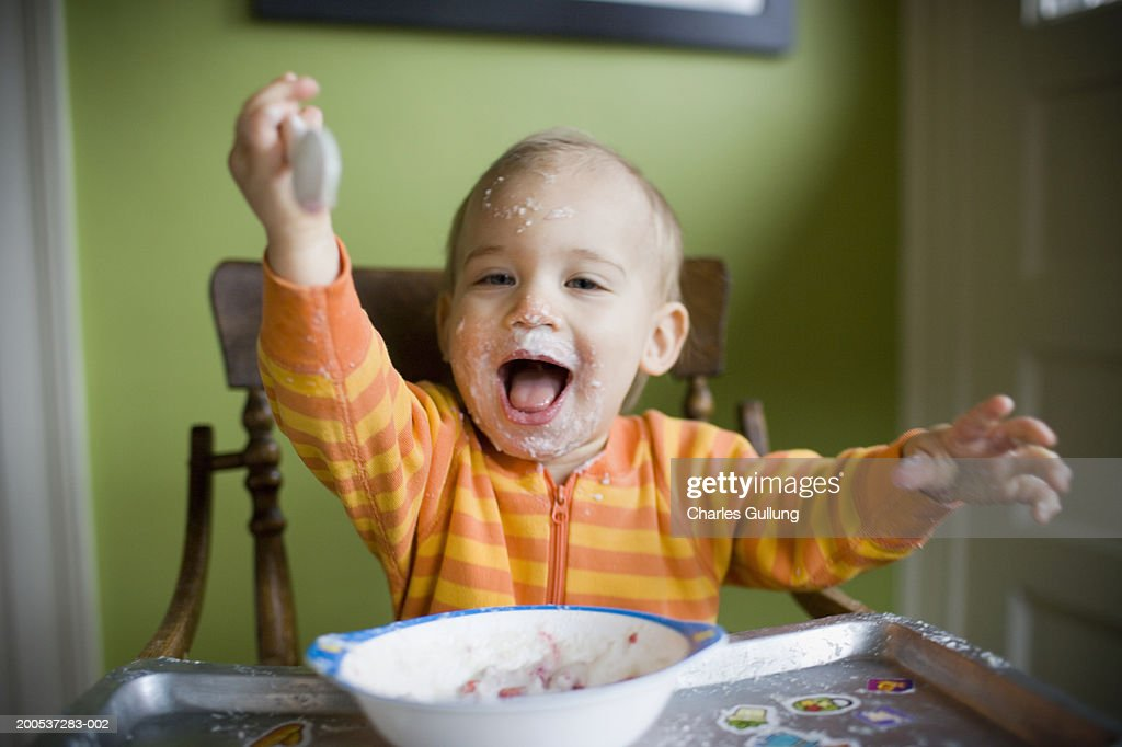 Baby boy (15-18 months) in high chair, face covered with food, smiling : Stock Photo
