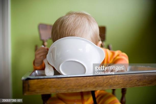Baby boy (15-18 months) in high chair, face down in bowl of food