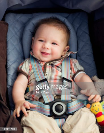 A baby boy in his car seat smiling