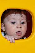 Baby boy is posing through a plastic window