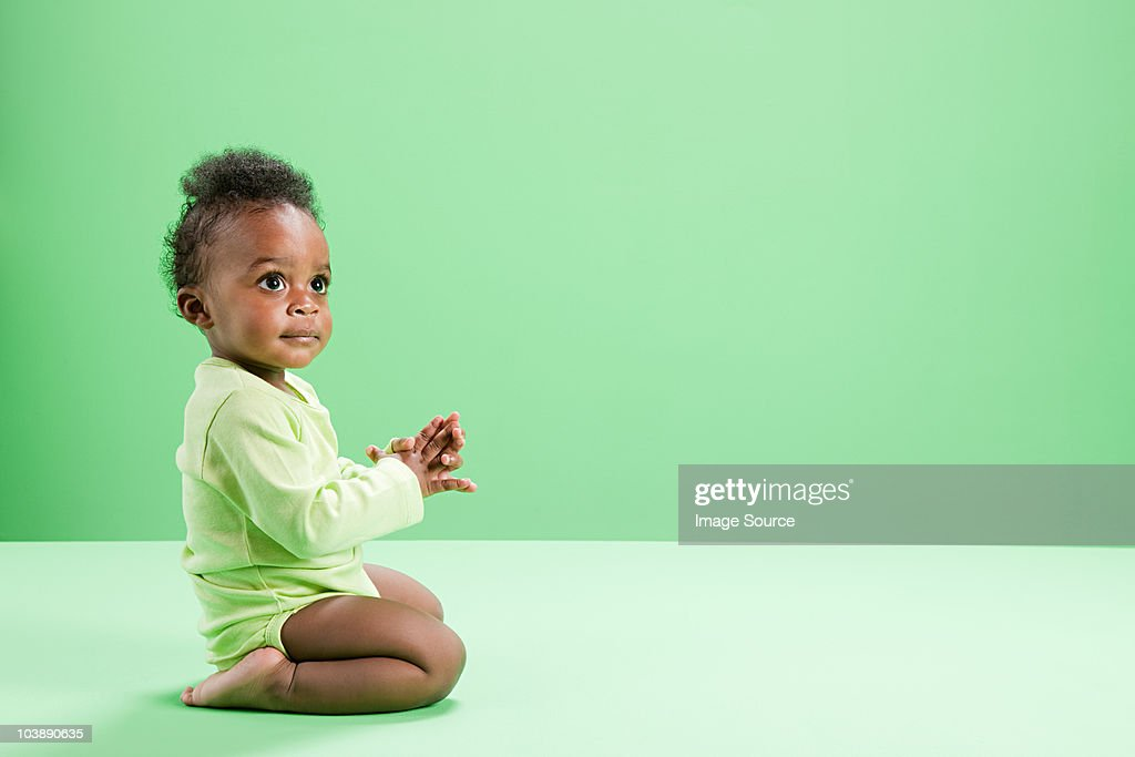 Baby boy kneeling against green background : Stock Photo