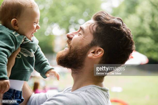 Baby boy laughing, is lifted in the air by his father in urban park.