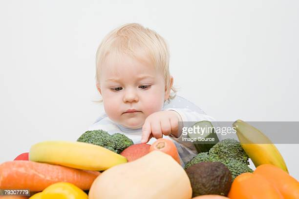 A baby boy looking at a stack of fruit and vegetables