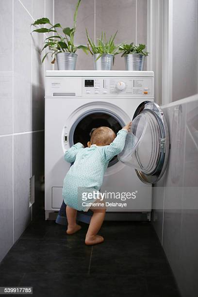 A baby boy looking at a washing machine's drum