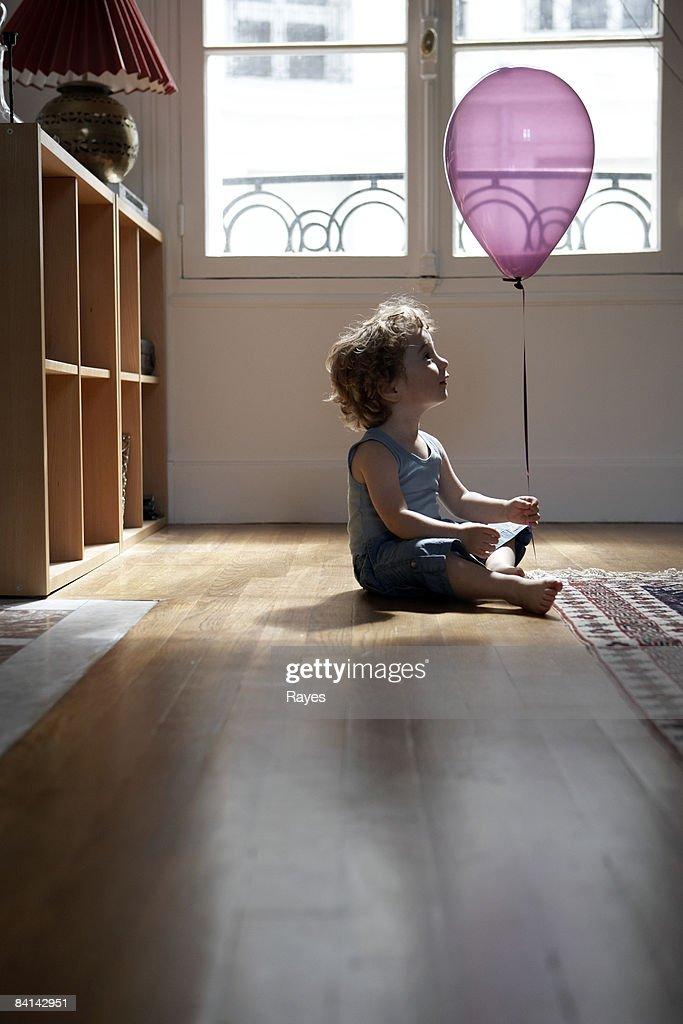 baby boy looking at balloon : Stock Photo