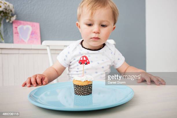 Baby boy looking at cupcake
