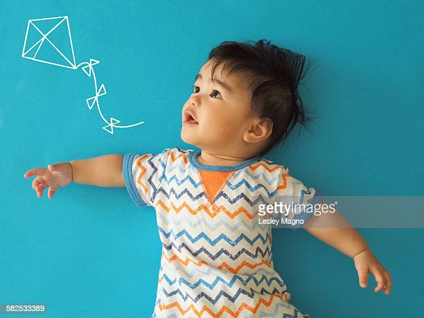 baby boy looking at kite in blue background