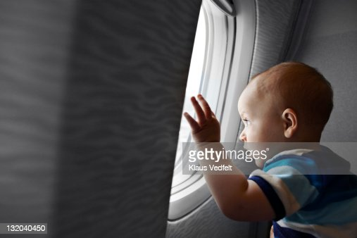 Baby boy looking fascinated out of airplane window : Stock Photo