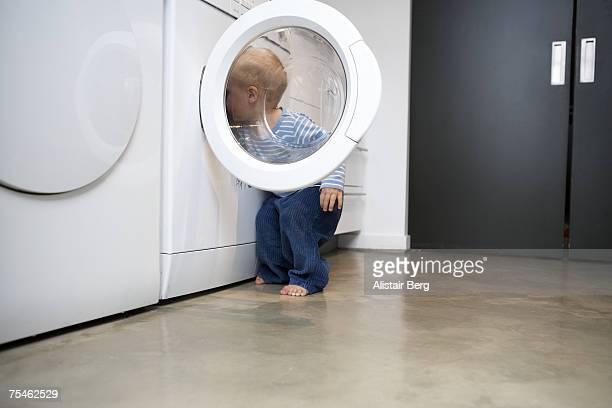 Baby boy (18-21 months) looking in washing machine