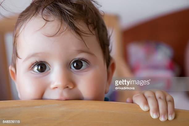 Baby boy looking over her cot