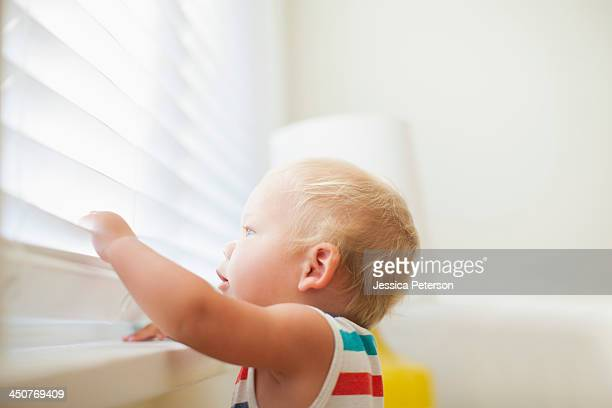 Baby boy (6-11 months) looking through window