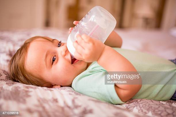 Baby boy lying down and drinking from a bottle