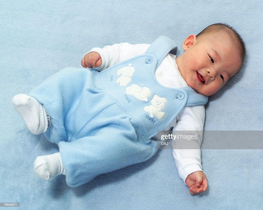 Baby boy lying on back, smiling, high angle view, portrait : Stock Photo