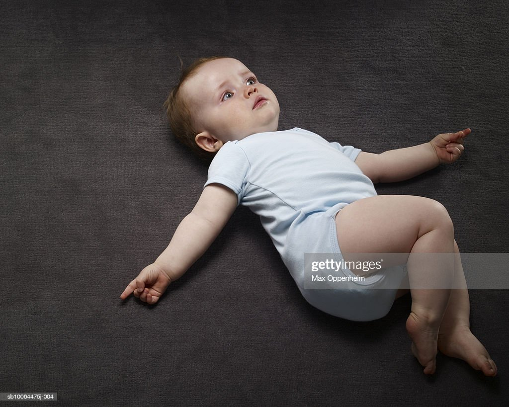 Baby boy (9-12 months) lying on floor, elevated view : Stock Photo