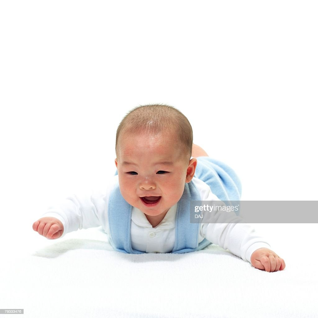 Baby boy lying on front, smiling, front view, portrait : Stock Photo