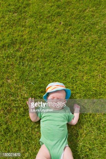 Baby boy lying on grass : Stock Photo