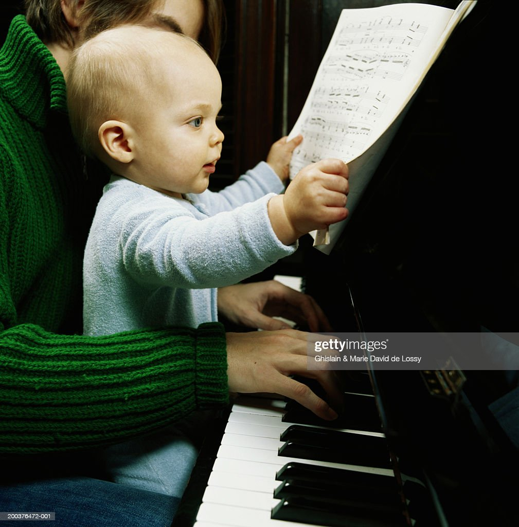 Baby boy (9-12 months) on father's lap holding score, father playing : Stock Photo