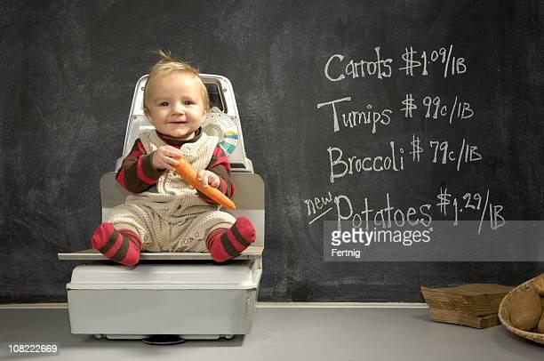 Petit garçon sur l'échelle de poids d'achat de denrées alimentaires