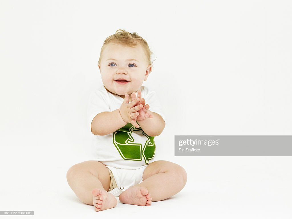 Baby boy (6-9 months) on white background, sitting and clapping hands