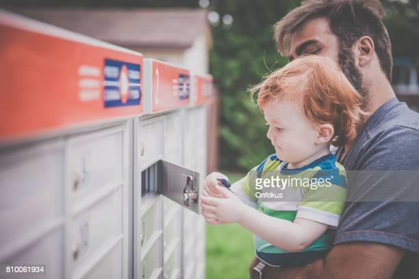 Baby Boy Opening a Mailbox with Parent