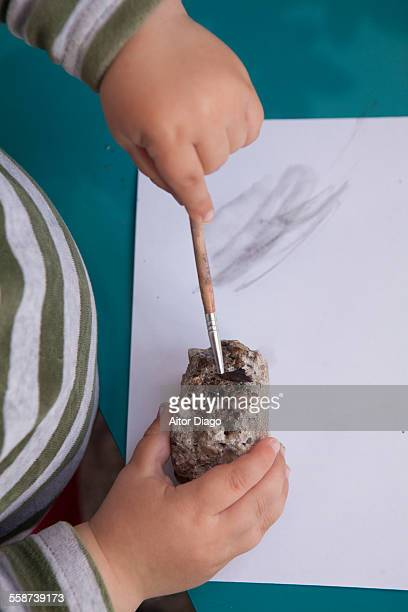 Baby boy painting a stone.