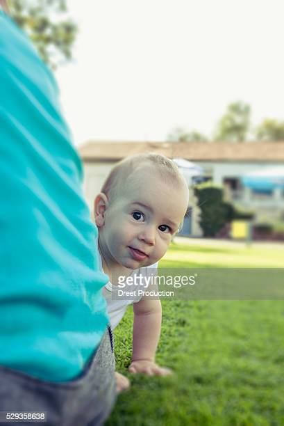 Baby boy peeping behind his mother in lawn, Munich, Bavaria, Germany