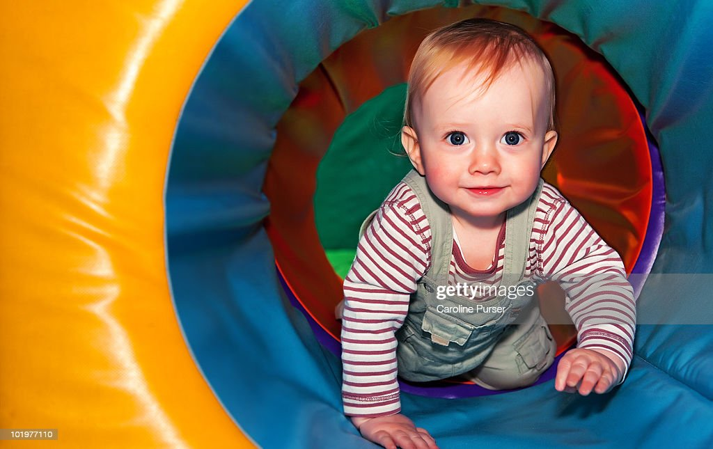 Baby boy playing in colourful tunnel : Stock Photo