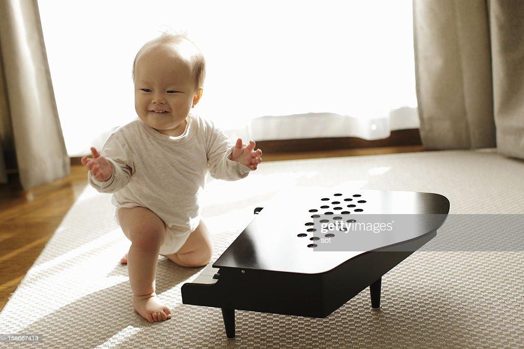Baby boy playing small piano : Stock Photo