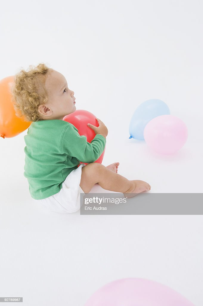 Baby boy playing with a balloon : Stock Photo