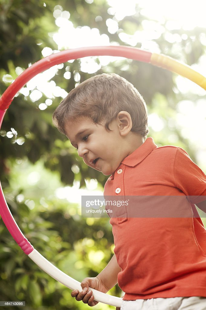 Baby boy playing with a plastic hoop : Stock Photo