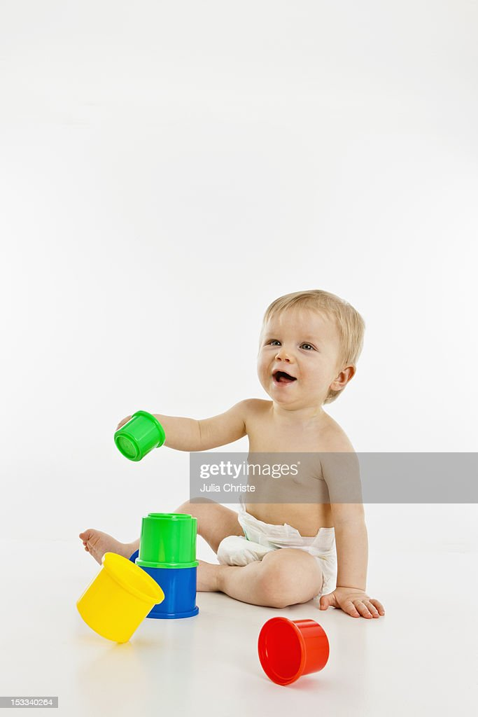 A baby boy playing with plastic cups : Stock Photo