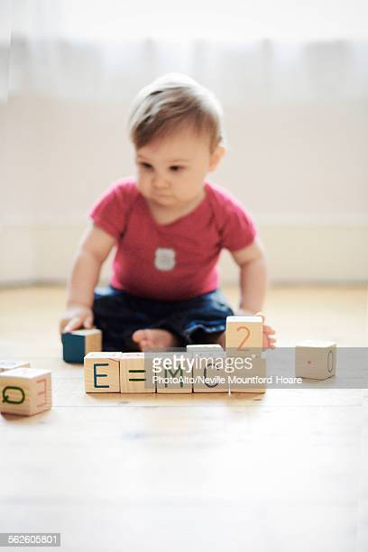 Baby boy playing with toy blocks arranged to read E=mc2