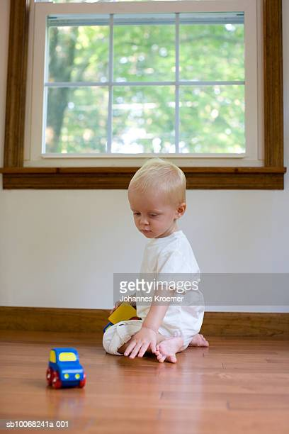 Baby boy (12-17 months) playing with toy car on floor at home