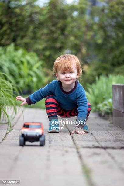 Baby Boy Playing With Toy Vehicle Outdoor