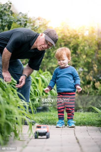 Baby Boy Playing With Toy Vehicle Outdoor with Grandfather