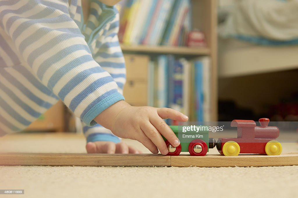 Baby boy playing with train set