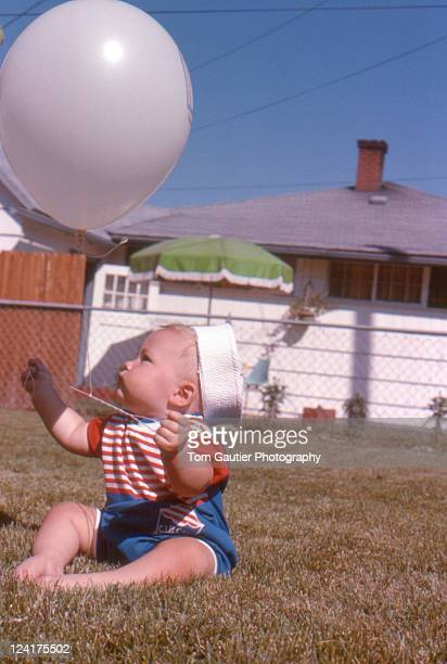 Baby boy plays with balloon in grass yard