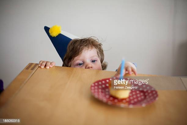 baby boy reaching for birthday cake birthday hat