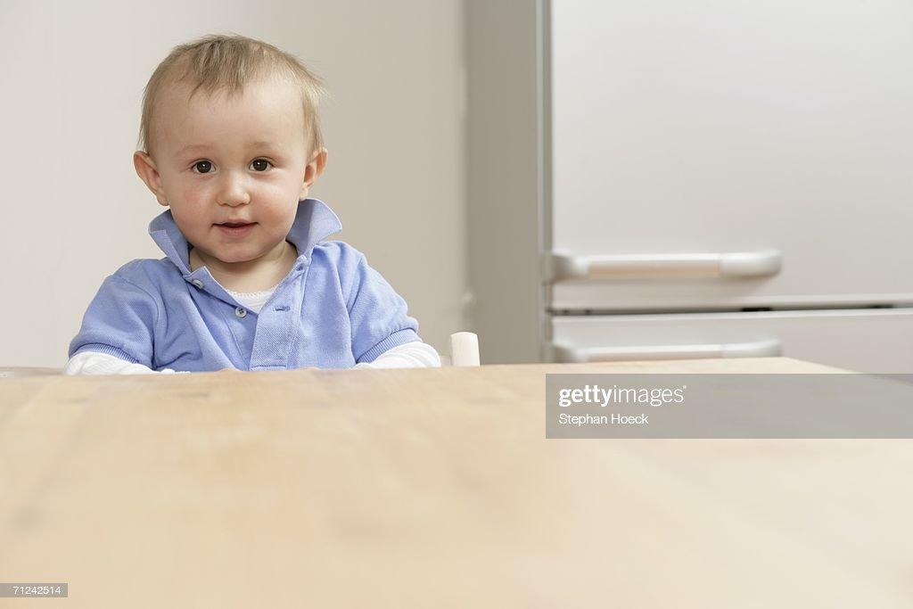 Baby boy sitting at table and looking at camera : Stock Photo