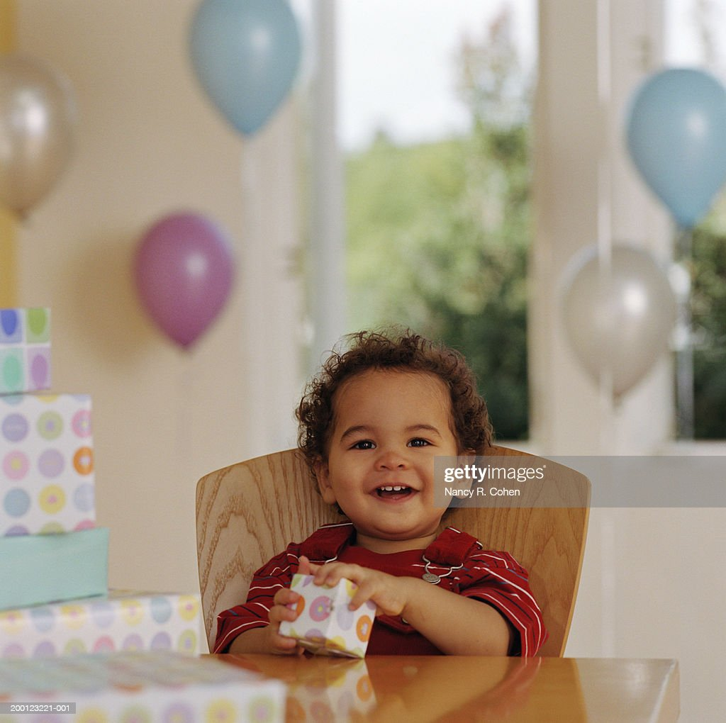 Baby boy (12-15 months) sitting at table, holding present, portrait
