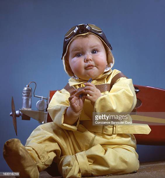 Baby boy sitting by toy airplane in aviator costume New York City
