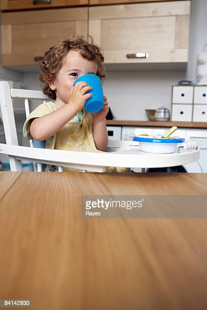 baby boy sitting in high chair drinking