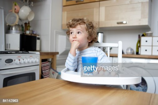 baby boy sitting in high chair looking thoughtful : Stock Photo
