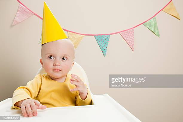 Baby boy sitting in highchair with bunting
