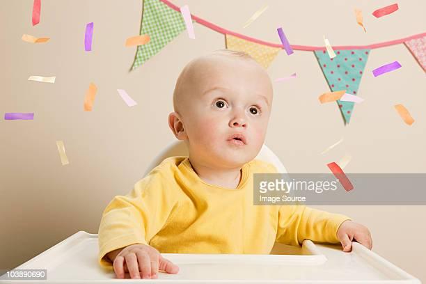 Baby boy sitzt im Hochstuhl mit Strampler