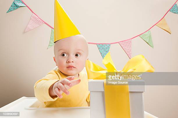Baby boy sitting in highchair with gift box
