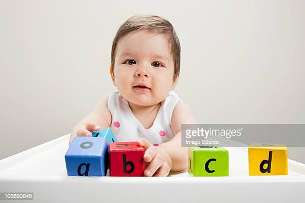 Baby boy sitting in highchair with wooden alphabet blocks