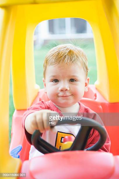 Baby boy (15-18 months) sitting in toy car, portrait